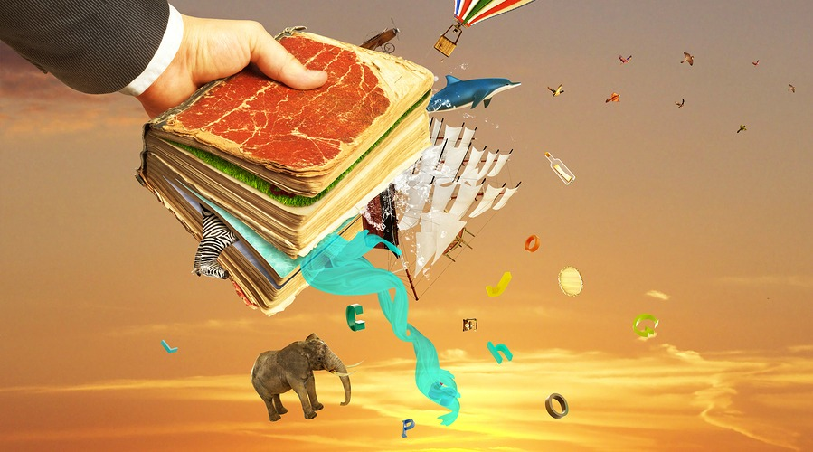 Concept of reading. Man's hand holding magic book with falling letters animals and other objects from this book. Concept of dreaming.